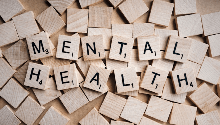 "Scrabble game pieces which spell out ""Mental Health"""