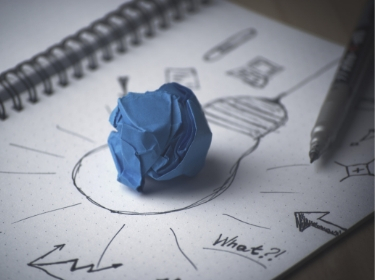 Un unmolded ball of blue clay sitting on a notepad with pen